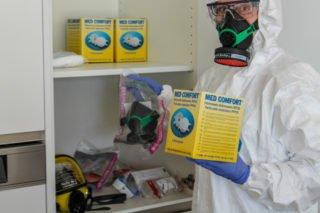 Mitarbeiterin Kristina Müller öffnet den Schrank mit den Vorräten an Schutzkleidung und Gummi-Masken. (Foto: Alexander Hauffen/SMMP)